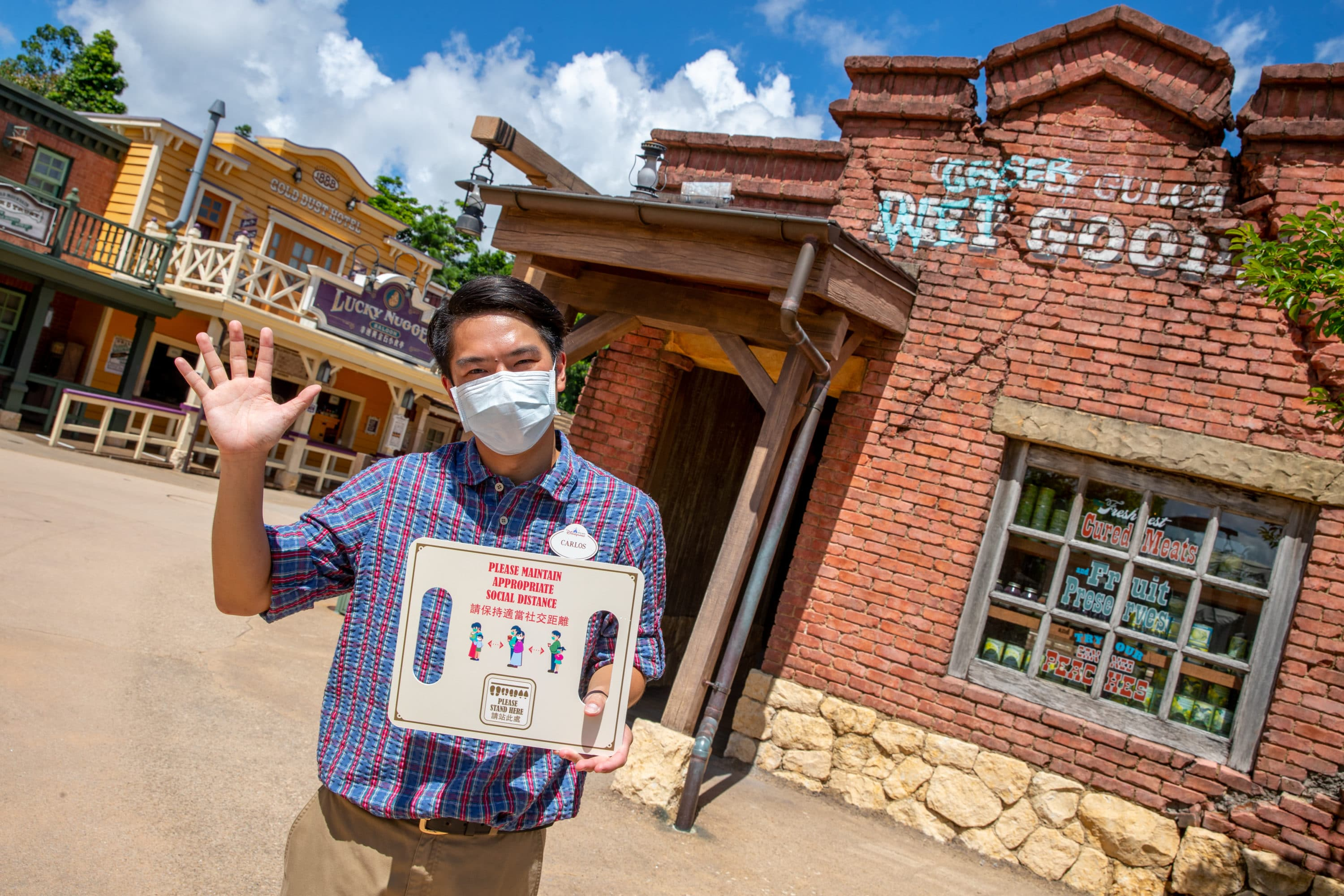 Cast Members welcome guests back to Hong Kong Disneyland and remind people about social distancing.